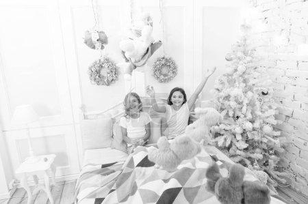 Photo pour Ambiance de Noël. Enfants heureux dans son lit à l'arbre de Noël. Jeux de l'enfance sur Noël et nouvel an. Petits enfants profiter de Noël. Petits enfants sont amuser de Noël. Petites filles jouent avec des jouets. - image libre de droit