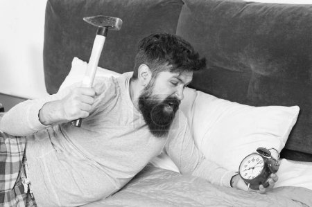 Photo pour Rattraper le sommeil manqué pendant le week-end. Réveil matinal. Homme réveillé malheureux avec réveil sonne. Bien que vous dormiez, vous pouvez vous réveiller en vous sentant comme si vous n'aviez pas dormi du tout. Étapes du sommeil . - image libre de droit