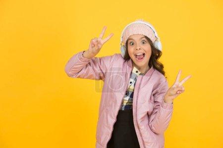 Photo pour L'apprentissage en ligne lui apporte la victoire. Happy child écouter de la musique en ligne. La petite fille montre des gestes de victoire. Apprendre en ligne. Cours de musique en ligne . - image libre de droit