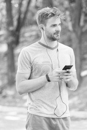 Photo pour Vivre un mode de vie mobile. Homme athlétique suivi de son activité avec l'application de téléphone mobile. Sportsman utilisant un appareil mobile et montre de fitness pour l'entraînement. Fit guy synchronisation fitbit données via Internet mobile . - image libre de droit