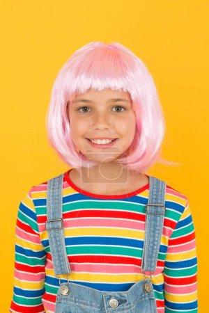 Photo pour Nouveau sourire nouveau look. Petite fille sourire en courte perruque rose. Joyeux sourire d'enfant fond jaune. Petit enfant avec un sourire blanc et sain. L'art dentaire. Soins dentaires en qui vous pouvez avoir confiance . - image libre de droit