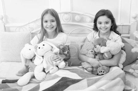 Photo pour Nous aimons à Noël. Petites filles jouent avec des jouets. Enfants heureux dans son lit à l'arbre de Noël. Petits enfants profiter de Noël. Petits enfants sont amuser de Noël. Jeux de l'enfance sur Noël et nouvel an. - image libre de droit