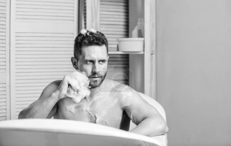 Photo for Man handsome muscular guy relaxing in bath. Spa wellness concept. Taking bath with soap suds. Treating yourself with hot or warm bath can feel like height of luxury. Pampering and beauty routine. - Royalty Free Image