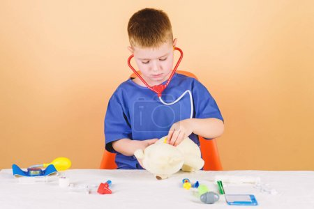 Photo for Health care. Kid little doctor busy sit table with medical tools. Medical examination. Medicine concept. Medical procedures for teddy bear. Boy cute child future doctor career. Hospital worker. - Royalty Free Image