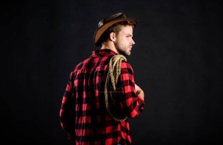 Photo pour La campagne. Homme de style vintage. Wild West retro cowboy. cow-boy au lasso. Ouest. homme chemise à carreaux sur le ranch. portrait de cow-boy de l'Ouest. wild west rodeo. homme en chapeau fond noir. - image libre de droit