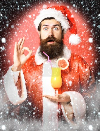 Photo for Handsome bearded santa claus man with long beard on surprised face holding glass of nonalcoholic cocktail in christmas or xmas sweater and new year hat showing ok. on red studio background - Royalty Free Image