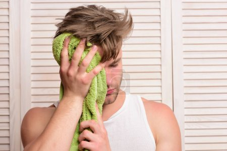 Photo for Athlete with strong muscles after shower. Man with green towel wipes his face. Guy with messy hair and sleepy face on wooden door background. Morning exercises and refreshment lifestyle concept - Royalty Free Image