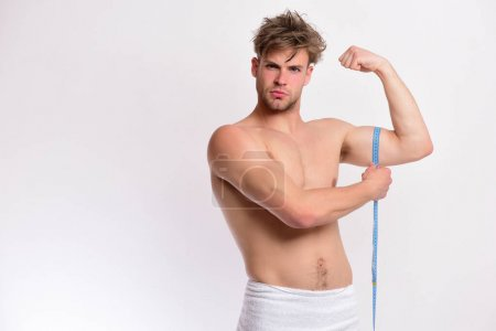 Photo for Guy with towel and flexible ruler isolated on white background. Measurement and size concept. Man with serious face and blue measuring tape around arm. Athlete with messy hair measures his muscles - Royalty Free Image