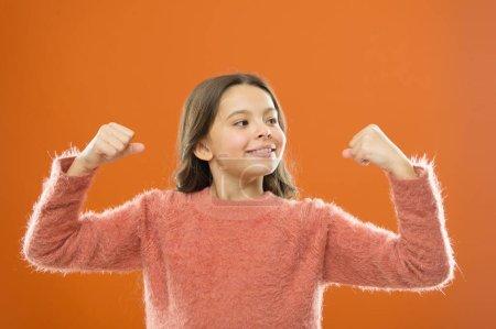 Photo pour Grandir fort et confiant. sentir le pouvoir d'elle-même. joyeux enfant orange toile de fond. enfance insouciante. sain et puissant. heureux jour des enfants. mignonne petite fille souriante. petit enfant montrer biceps . - image libre de droit