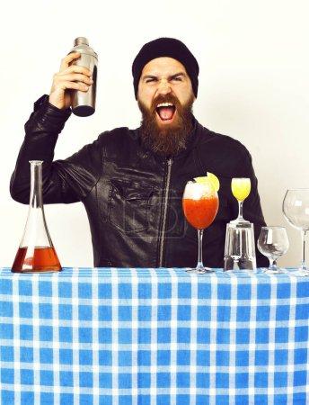 Photo pour Barbu, longue barbe. Brutal hipster caucasien avec moustache dans le style rock noir tenant shaker et verres de cocktails alcoolisés avec tir sur blue plaid damier isolé sur fond blanc - image libre de droit