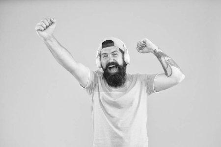 Photo pour Écouteurs conçus pour offrir un son propre. Homme à la mode portant des écouteurs sur fond jaune. Homme barbu écoutant de la musique dans un casque stéréo. Hipster utilisant des écouteurs sans fil modernes . - image libre de droit