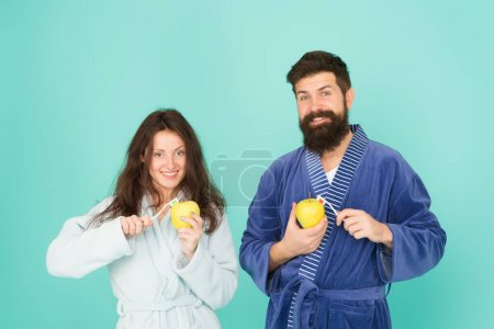 Photo for Couple in bathrobe grooming. bearded man and girl healthy smile. family couple hold apple with toothbrush. having healthy and strong teeth. morning routine. personal care in morning. Oral hygiene. - Royalty Free Image