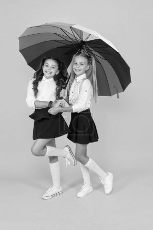 Photo for Autumn style. Happy small girls holding rainbow style umbrella on yellow background. Little children smiling in school style. Giving school fashion a sense of style. - Royalty Free Image