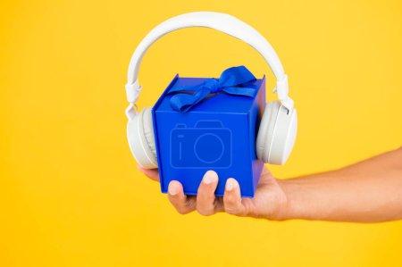 Photo pour Music gift conept. boîte cadeau avec écouteurs. les hommes tiennent la main présente toile de fond jaune. casque moderne. ce qui est dedans. vente d'accessoires audio. Noël cadeau de musique. présent musical. livraison rapide. - image libre de droit