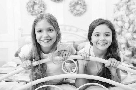 Photo pour Joyeux Noël à mon cher ami. Petits enfants dans la chambre à coucher avec arbre de Noël. Petites filles dans son lit le soir de Noël. Heureux, les enfants ont l'esprit de Noël. Traditions de la petite enfance. - image libre de droit