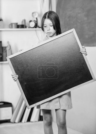 Photo pour Pour faire la liste. Retour à l'école. Bonne journée des enseignants. 1 septembre. La petite fille démontrent le tableau blanc. Petite fille d'école avec l'espace de copie de tableau noir. Informations importantes. Publicité à l'école. - image libre de droit