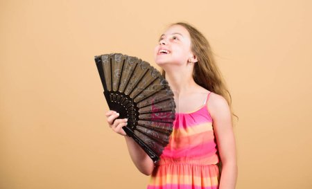 Photo pour Refroidissement et ventilation. Chaleur estivale. De l'air frais. Fille gosse se ventilant avec ventilateur. Système de conditionnement. Contrôle de la température. Climatiseur. Agitant pour créer de l'air actuel. Petite fille agitant ventilateur élégant . - image libre de droit