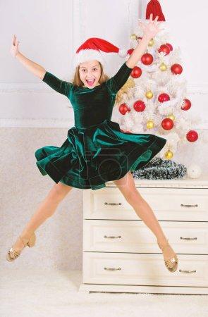 Photo pour Enfant émotionnel ne peut pas arrêter ses sentiments. Célébrer le concept de Noël. Fille en robe de saut d'obstacles. C'est Noël. Jour que nous avons attendu toute l'année enfin ici. Jeune fille excité par saut de Noël mi air. - image libre de droit