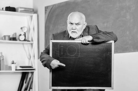 Photo for Look here. information is here. place for copy space. Mature teacher man hold chalk board. exam and graduation results. senior man teacher with empty blackboard. back to school. Education concept. - Royalty Free Image