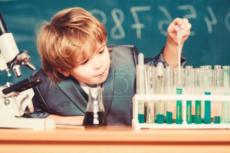 School education. Explore biological molecules. Toddler genius baby. Boy near microscope and test tubes in school classroom. Technology and science concept. Kid study biology and chemistry in school