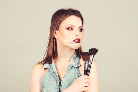 Photo pour La fille applique des ombres d'oeil de poudre. Vous avez l'air bien et confiant. Maquillage lèvres foncées. Femme attirant appliquant la brosse de maquillage. Fournitures de maquillage professionnelles. Concept d'artiste de maquillage. Mettre l'accent sur la féminité. - image libre de droit