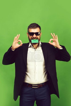 Photo for Man with beard in suit holds green business card in teeth. Businessman with empty card shows OK signs. Guy with happy face and sunglasses isolated on green background. Business and success concept - Royalty Free Image