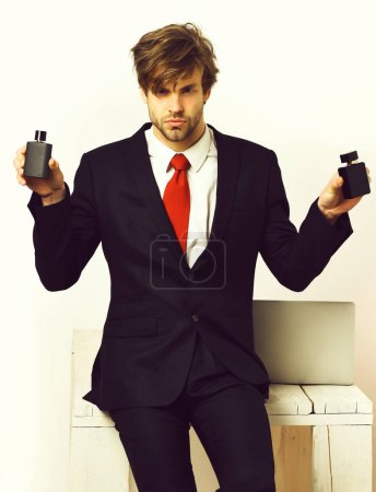 Photo for Bearded man, short beard. Caucasian stylish business man with moustache in elegant black suit and red tie posing with perfumes in studio isolated on white background - Royalty Free Image