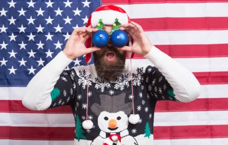 Photo for Patriotic surprise. Surprised hipster hold baubles as glasses. Bearded man look with surprise. Santas surprise celebration. Creating fun surprise. Christmas and new year. Holiday season. - Royalty Free Image