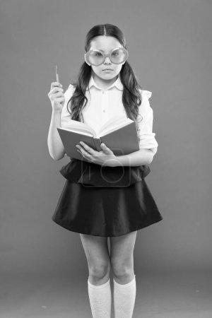 Literatur studieren. Schüler lernen gerne. kleines Mädchen genießt ihre Schulzeit. glückliches kleines Schulmädchen bereit für den Unterricht. Nettes Kind mit Buch. nur Weisheit, wenn man weiß, dass man nichts weiß. Fremdsprache studieren