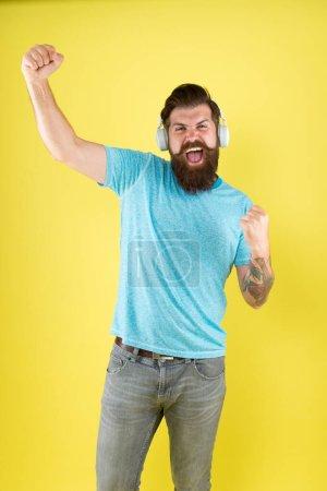 Photo pour Né pour gagner. Joyeux gagnant qui écoute de la musique. Un homme barbu fait un geste de vainqueur. Hipster épilé fort fond jaune. Célébration de la victoire. Toujours un gagnant. - image libre de droit