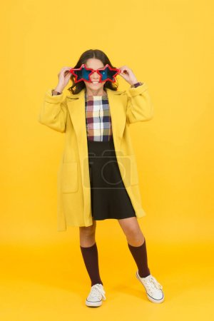 Photo pour Les filles joyeuses portent des lunettes pour s'amuser. Des lunettes de soleil en forme d'étoile froide pour les enfants. Concept des étoiles. Célébration et popularité. Écolière populaire. Célébrité du costume de carnaval. Rock star. Célébration des fêtes. - image libre de droit
