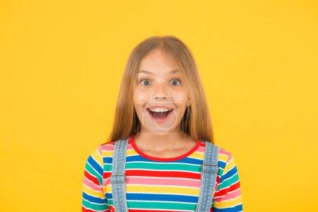 Photo pour Joyeuse journée des enfants. bonheur d'enfance. gai hipster fille vêtements colorés. concept optimiste. petite fille fond jaune. mode enfant d'été. humeur positive des enfants. Portrait de bonheur enfant . - image libre de droit
