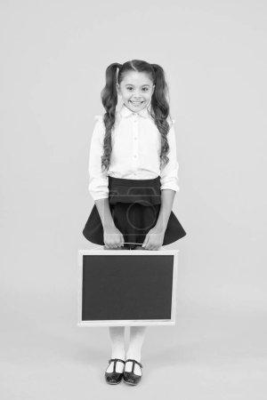 Vorbereitung eines kleinen Kindes auf die Schule. Kleines Mädchen mit schwarzem Brett auf gelbem Hintergrund. Kleines Kind mit leerer Tafel für Ihren Text. Kleines Schulkind hält Tafel für Werbung, Kopierraum