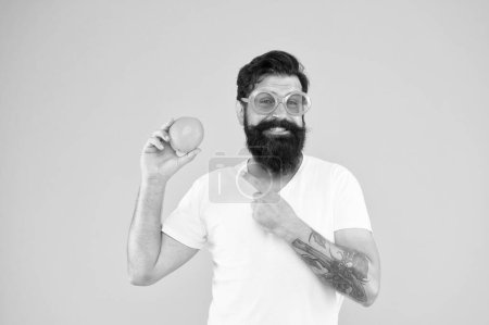 Photo for Its always better when its natural. Hipster pointing at natural orange fruit on yellow background. Bearded man with natural vitamin food. Be smart, eat natural. - Royalty Free Image