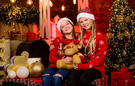 Photo for Love is in the air. Happy Holidays. small girls has xmas mood. Happy New Year. sisters spend family holiday together. santa children toy bear. winter shopping sale kid store. Christmas party time. - Royalty Free Image