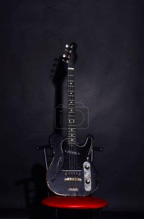 Photo pour Guitare électrique debout sur chaise rouge. Instrument de musique à quatre cordes pour jouer du métal ou du jazz. Musique et concept de hard rock. Guitare de couleur noire foncée sur fond noir. - image libre de droit