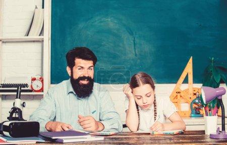 Photo pour Trop de travail. leçon privée. journée de la connaissance. Enseignement à domicile. fille étudier avec le père. Journée des professeurs. petite fille enfant avec barbu professeur homme dans la salle de classe. retour à l'école. Enseignement privé . - image libre de droit