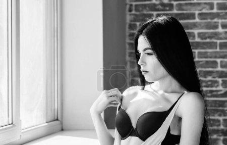 Photo pour Costume sexuel pour le plaisir. Passionné amant mystérieux. Profiter de la lumière du soleil du matin. Poitrines sexy de fille sensuelle détendant près du rebord de fenêtre. Lingerie sexy femelle attirante à la maison. Sexualité renversante. - image libre de droit