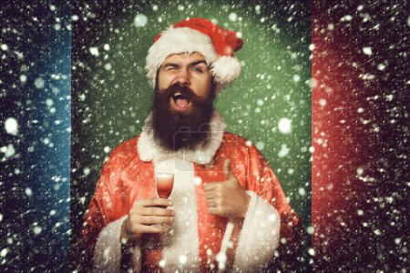 Photo for Handsome bearded santa claus man with long beard on funny face holding glass of alcoholic shot in red christmas or xmas sweater and new year hat. showing cool on colorful studio background - Royalty Free Image