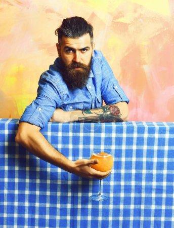 Photo pour Barbu, longue barbe. Brutal caucasien hipster tatoué avec moustache en chemise en denim tenant cocktail frais alcool tropical bleu plaid damier sur fond coloré de texture - image libre de droit
