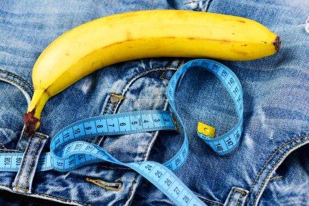 Photo pour Santé et sexualité masculine concept. Mens denim pantalon entrejambe avec banane imitant des organes génitaux masculins. Kinky fruits avec du ruban de mesure bleu sur les jeans, mise au point sélective. Entrejambe de jeans, gros plan. - image libre de droit