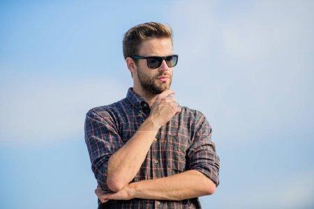 UV-Schutzkonzept. Perfekte Vision. Sehen Sie es klar. Schöner Typ mit Sonnenbrille. Hipster-Mann mit trendiger Sonnenbrille. Modische Sonnenbrille. Mann Brille Modell im Freien blauer Himmel Hintergrund