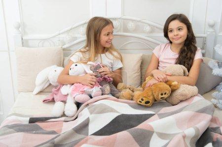 Photo pour Hope Santa est bon pour nous cette année. Jeux d'enfants sur Noël et Nouvel An. Les petites filles jouent avec les jouets. Les petits enfants aiment Noël. Les petits enfants s'amusent à Noël. Bons enfants au lit à la veille de Noël. - image libre de droit