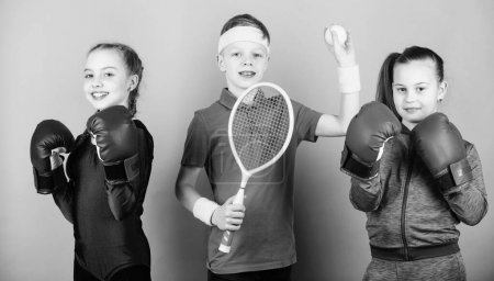 Photo for Sporty siblings. Ways to help kids find sport they enjoy. Friends ready for sport training. Child might excel completely different sport. Girls kids with boxing sport equipment and boy tennis player. - Royalty Free Image