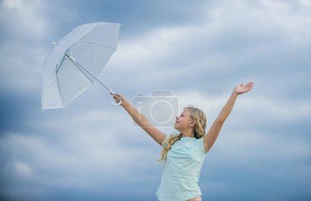 Photo pour Enfant insouciant à l'extérieur. Prévisions météorologiques. Prêt pour tout temps. Le temps change. De l'air frais. Fille avec fond ciel nuageux parapluie. Liberté et fraîcheur. Joyeuse journée des enfants. Profiter de la facilité. - image libre de droit