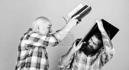 Photo for Confrontation. technology battle. Modern life. youth vs old age. business approach. father and son. family generation. two bearded men. Vintage typewriter. retro typewriter vs laptop. New technology. - Royalty Free Image