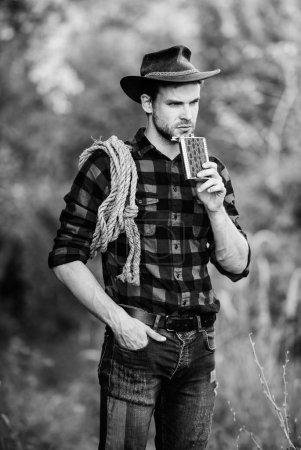 Photo pour Ouvrier de ranch de cowboy. Cow-boy brutal buvant de l'alcool. Fond beau de nature de cowboy d'homme. Du whisky Bourbon. Culture occidentale. Homme utilisant la corde de prise de chapeau et le flacon. Cowboy américain d'outil de Lasso. - image libre de droit