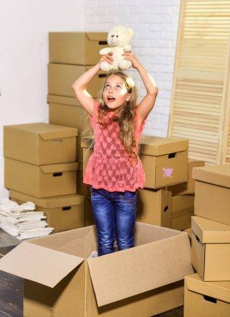 Photo pour Heureuse petite fille avec jouet. Boîtes en carton - déménagement dans une nouvelle maison. heureux enfant boîte en carton. Concept mobile. nouvel appartement. achat de logements neufs. Votre nouvelle vue attend . - image libre de droit