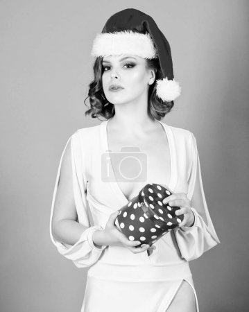 Photo pour Robe blanche sexy femme séduisante dame usure et bonnet rouge. Cadeau du père Noël. Jeune fille tenir boîte de cadeau de Noël d'ouverture. Jeune fille fêter Noël. Jeune fille porter chapeau de père Noël. Elle a présent pour vous. - image libre de droit