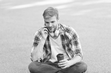 Photo for Morning vibes. man sit on ground. carefree student in headset. online education. listen music. man checkered shirt speak on phone. student relax and recharge. coffee to go. guy drink coffee. - Royalty Free Image